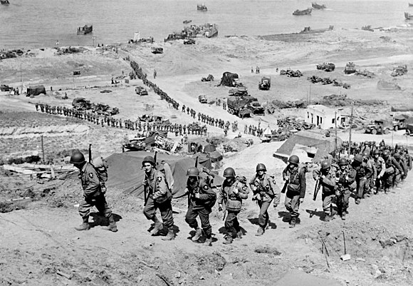 2nd Infantry Division troops and equipment going up the bluff via the E-1 draw on D+1, June 7. They are going past WN-65 that defended the route up the Ruquet Valley to Saint-Laurent-sur-Mer. 2nd Infantry Division, E-1 draw, Easy Red sector, Omaha Beach, D+1, June 7, 1944.jpg