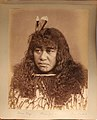 A Maori girl, Marau Kingi, poses against a plain background. She has shoulder length hair decorated with feathers and facial (56f9ad67-b09e-4279-a34b-0588b9ccc5af).JPG