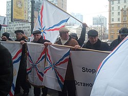 Warmly-dressed men holding Assyrian flags