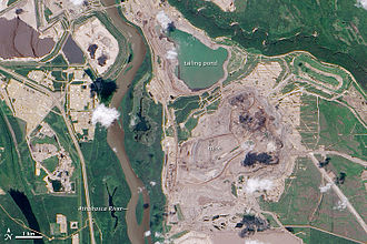 Athabasca oil sands - Mining operations in the Athabasca oil sands. Image shows the Athabasca River about 600m from the tailings pond. NASA Earth Observatory photo, 2009.