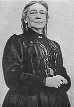 Half length portrait of a serious elderly woman in a black Victorian dress, standing with hands clasped at her waist