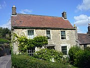 Two storey stone house with red roof. Partially obscured by vegetation