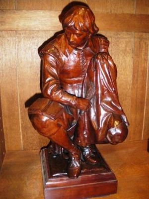 "Valet - Carving of ""Bazin"", the valet to Aramis, of The Three Musketeers, was a studious person who later became a lay brother. (Thomas Nicholls carves him brushing his master's clothes whilst studying theology)."
