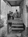 Bill Daniels, a miner, and his two daughters on the front porch of their three room house for which they pay $7... - NARA - 540998.tif