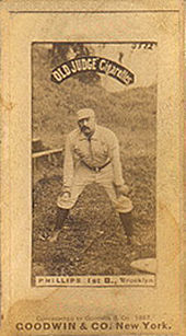 A man in a baseball uniform is crouched slightly with his hands on his knees.