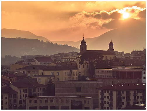 Avellino, scorcio con Duomo e Torre dell'orologio che svettano al tramonto. In basso il Teatro Gesualdo.