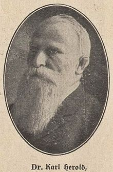 "An oval black and white photograph of the politician with white beard, with the caption ""Dr. Carl Herold"" below it."