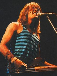 Thirty-one year old Williams is at a microphone with teeth clenched, he strums his right hand on the bass while the left is out of view. His red-brown hair is over collar length. He wears a singlet and has a leather arm band.