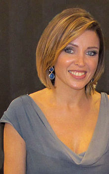 A woman wearing a grey shirt and smiling.