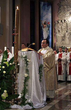 Paschal candle - Deacon chanting the Exultet beside a Paschal candle.