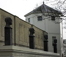 Four evenly-spaced sculptures of bald male heads with slightly different facial expressions, each standing on a black rectangular plinth on a flat white surface in front of a yellow-brick wall and an octagonal grey-roofed tower.