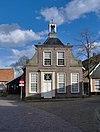 foto van Drostenhuis, pand met afgeknotte halsgevel, thans beëindigd met zandstenen lijst