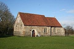 Una pequeña iglesia de piedra simple con un techo de tejas rojas visto en ángulo, con la nave en primer plano y un pequeño presbiterio más allá