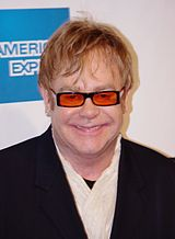 A Caucasian man with light brown hair. He is wearing black framed glasses with orange lenses and a black suit over a white shirt. Behind him is a white wall with a blue square.