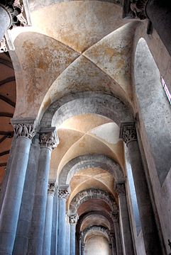 A narrow space with grey columns with ornate capitals supporting a plastered cross vault without ribs.
