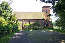 A photograph of a simple country church, with its square western tower in brick to the right and the older stone eastern end, slightly obscured by trees to the left.