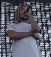 A man is rapping into a microphone while standing on a stage.