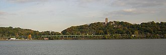 Fort Tryon Park - A view of the park from the Hudson River; The Cloisters can be seen at the top of the hill on the right. The green elevated highway is the Henry Hudson Parkway