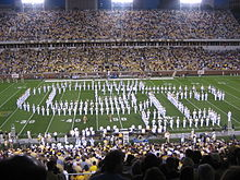 There is a large football stadium with yellow bleachers and green grass, seen at night. The band is on the field facing the viewer, wearing white uniforms, holding instruments, and arranged to form an interlocking GT. Many people are in the stands.