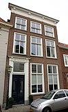 foto van Hoog huis met lijstgevel in Empire stijl; kroonlijst op consoles; ingang omlijst en versierd met consoles, bladwerk en een tandlijst