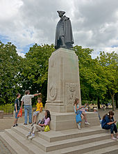 A dark brown statue of a man in 18th-century military uniform, including tricornered hat, on a light tan stone pedestal. Around its base people dressed primarily in T-shirts and shorts are lounging. There are trees a short distance beyond