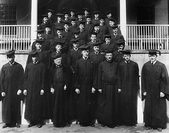 Thirty-four men in black robes and square academic caps stand on an outdoor staircase.