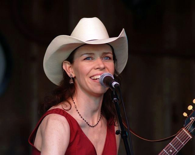 A slender, middle-aged woman with long brown hair plays guitar and sings into a microphone. She wears a cowboy hat and a red dress.