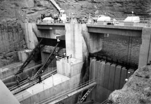 Risks to the Glen Canyon Dam - Spillway gates at Glen Canyon Dam during 1983 flood. Note the flashboards installed atop to prevent water from overtopping the gates.