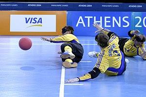 Três atletas, usando vendas, estão deitados na quadra, durante uma partida de goalball.