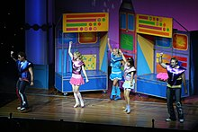 A distant stage shot of five performers, all are in bright clothes and have their right hand raised in the air. All have headset microphones, most are facing to their right and dancing. Behind them are movable sections, each is brightly coloured.