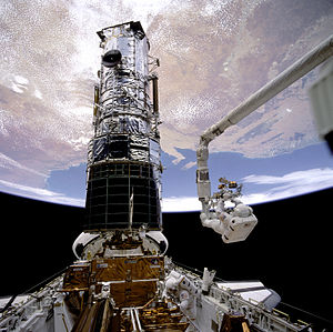 Story Musgrave - Musgrave, anchored on the end of the Canadarm, prepares to be elevated to the top of the Hubble Space Telescope to install protective covers on the magnetometers as part of STS-61