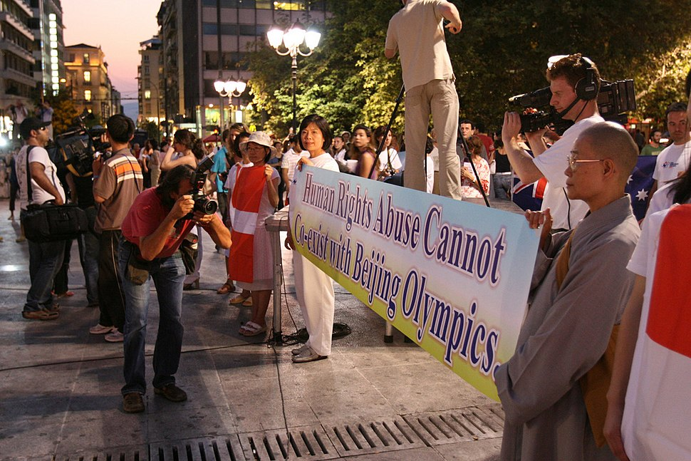 """A crowd of protestors along a street displays a banner reading """"Human Rights Abuse Cannot Co-exist with Beijing Olympics"""". Near the centre of the image, a photographer holds a camera level with the banner while looking through the viewfinder."""