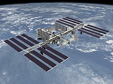 A planform view of the International Space Station is backdropped by the limb of the Earth. In view are the station's four large, blue-colored solar array wings, two on either side of the station, mounted to a central truss structure. Further along the truss are six large, white radiators, three next to each pair of arrays. In between the solar arrays and radiators is a cluster of pressurised modules arranged in an elongated T shape, also attached to the truss.