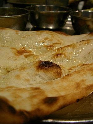 English: Indian Naan bread and curry served in...