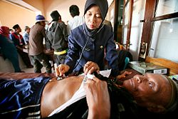 Indonesian nurse examines patient.JPG