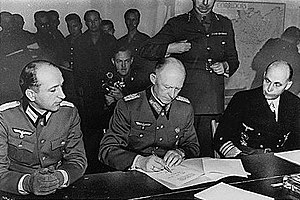 Nero Decree - Alfred Jodl (between Major Wilhelm Oxenius to the left and Generaladmiral Hans-Georg von Friedeburg to the right) signing the German Instrument of Surrender at Reims, France 7 May 1945