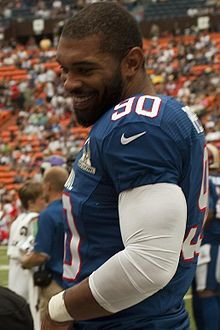 An American football player wearing a blue jersey with the number 90 while smiling.