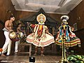 Kathakali performance with musicians, green face costumed Deva and black faced costumed Asuri.jpg