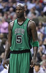 "A man, wearing a green jersey with a word ""BOSTON"" and the number ""5"" written in the front, is standing on a basketball court."