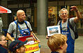 KunstHausierer Klaus-Dieter Gleitze, rechts, Hermann Sievers vom Künstlernetzwerk SCHUPPEN 68, Walk Act als Kunst-Installateure mit Bauchladen, Solidaritätstafel 2012 in Hannover.jpg