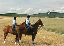 Two mounted policewomen in field, looking at helicopter
