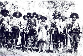 Lampião - Lampião and some of his cangaceiros. Lampião is left of centre, to the right of him is Maria Bonita. The distinctive leather hats with upturned brims and leather clothes can be seen. The men have Mauser rifles, a great deal of ammunition and several have long peixeira knives thrust though their waist-belts.