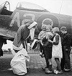Leading Aircraftman Fred Fazan dressed as Santa Claus hands out presents to Dutch children at No. 122 Wing's airfield at Volkel, Holland, 13 December 1944. CL1729.jpg