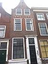 foto van Pand met tuitgevel met korfbogen boven de vensters. Lodewijk XIV/XV deuromlijsting. Hardstenen stoep met palen