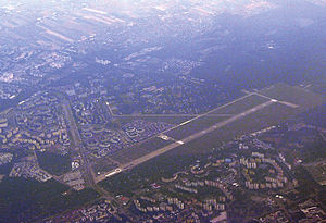 Warsaw Babice Airport - View of the airport from the air to the southwest. The photo draws attention to Powstańców Śląskich Street which is a street on the path of the former second runway. The paved runway 10R/28L in use is only a part of its former length.