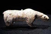 Photographie en couleurs sur fond noir et vue du dessus d'une statuette en ivoire représentant un ours des cavernes, ses pattes amputées reposant sur un socle de verre.