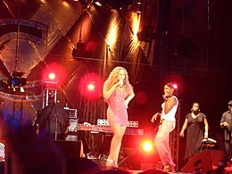 A woman wearing a pink ensemble, performing in a concert.
