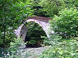 Arched bridge leads away over a rushing river. Bushes and trees crowd on all sides.