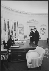 Black and white image of three men meeting in the oval office