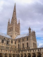 A sturdy tower with Norman details supports a delicate spire framed by four pinnacles.